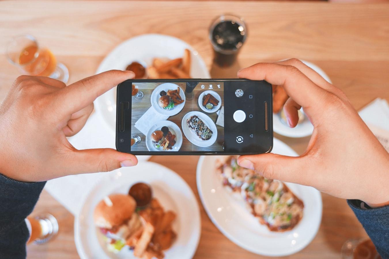 Un influenceur prenant la photo d'un repas pour la publier sur Instagram