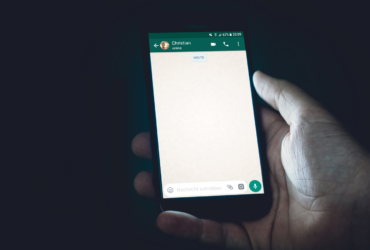 Un homme tenant un téléphone qui affiche une conversation sur WhatsApp.