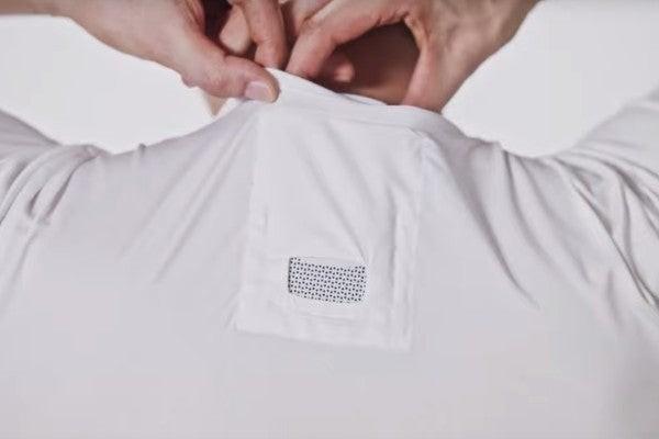 Un homme rangeant le Reon Pocket à la base de son cou dans le tee-shirt spécial prévu par Sony.
